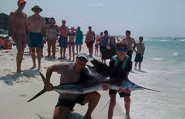 Chuck and CJ Moeling, from  Newnan, Georgia proudly hold their sailfish on Seagrove Beach.