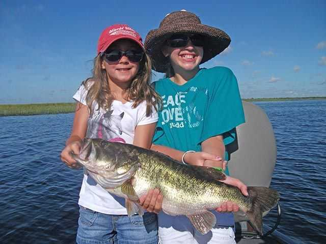 Mackenzie and Ryan Beatty from Stuart share the load of a big Okeechobee bass they caught in August. Photo credit: Capt. Mike Shellen.