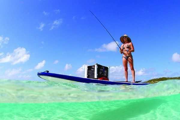 Beautiful woman fishing from paddle board