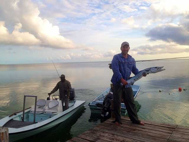 Chris from the U.S.A. with a barracuda caught on the flats of East Grand Bahama Island. PHOTO CREDIT: Firefly Bonefishing.