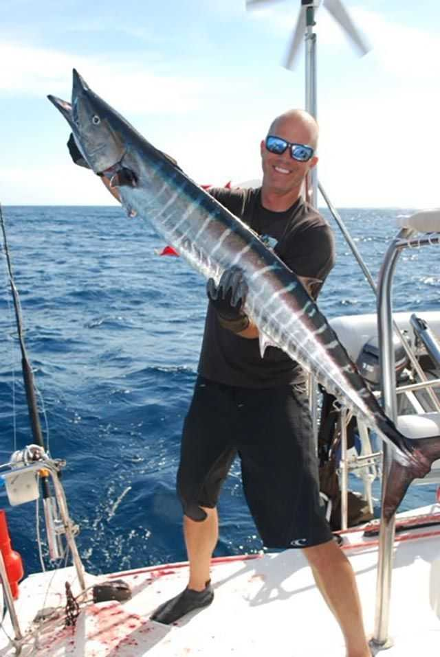 """Sébastien Dubé from Quebec, Canada, with a 25-pound, 50-inch wahoo caught in Rudder Cay, Exuma, on """"Catamaran One Life."""" PHOTO CREDIT: Marie-Claude Slovinski."""