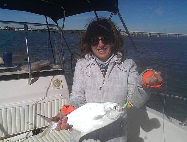 Monique Walker with a pompano caught in the Fort Pierce Inlet with Doc's Goofy Jigs on a chilly day. PHOTO CREDIT: Artie Olsen.