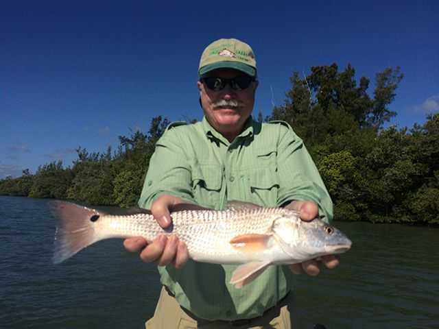 Duncan Haley with a nice slot redfish caught on the grass flats in Fort Pierce. PHOTO CREDIT: Capt. Charlie Conner.
