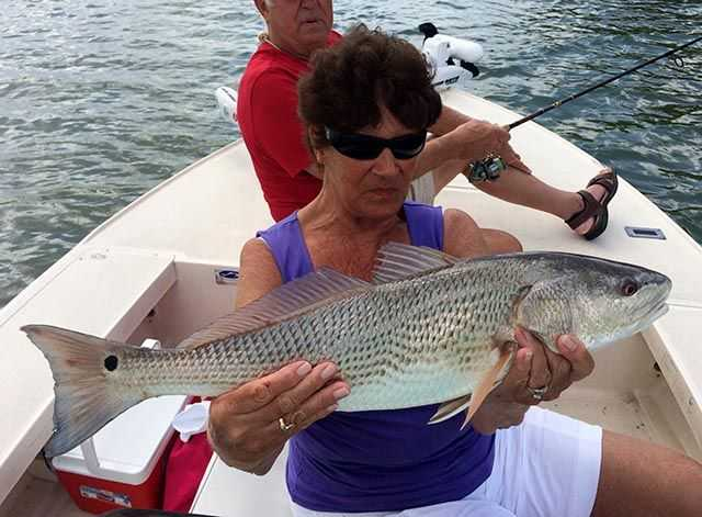 Jean with one of her four redfish caught on the grass flats of Fort Pierce. PHOTO CREDIT: Capt. Charlie Conner.