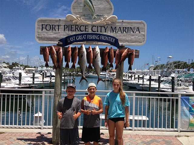 Three tired kids after catching 13 mangrove snappers on a recent July fishing charter. PHOTO CREDIT:  Capt. Rich Kluglein / Fins Sport Fishing Charters.