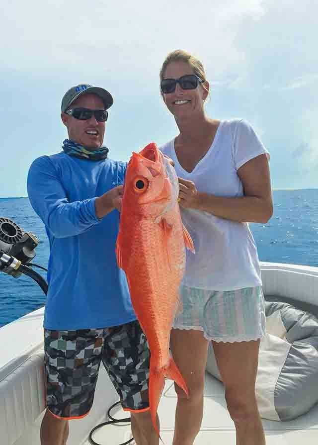 "Sasha Lickle with a pretty queen snapper caught off Green Turtle Cay aboard ""ADHD"", which is owned by Lamont Harris (on the left). PHOTO COURTESY of Green Turtle Club."