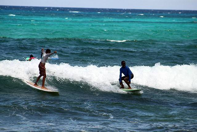 Party wave! Noah and Mattheo at Bahamas Out Island Adventurers Surf Camp IX this summer. PHOTO CREDIT: Liz Heiberg-Glucksmann.