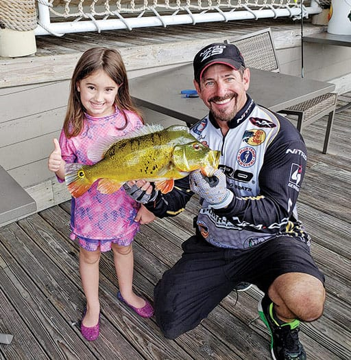 Five year old Kaylie Leavelle caught her first fish with a little help from Capt. Neal.