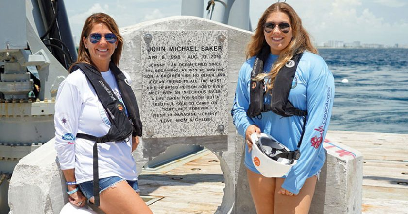 Johnny's mother and sister, Jamie and Chloe Baker, in front of memorial plaque.