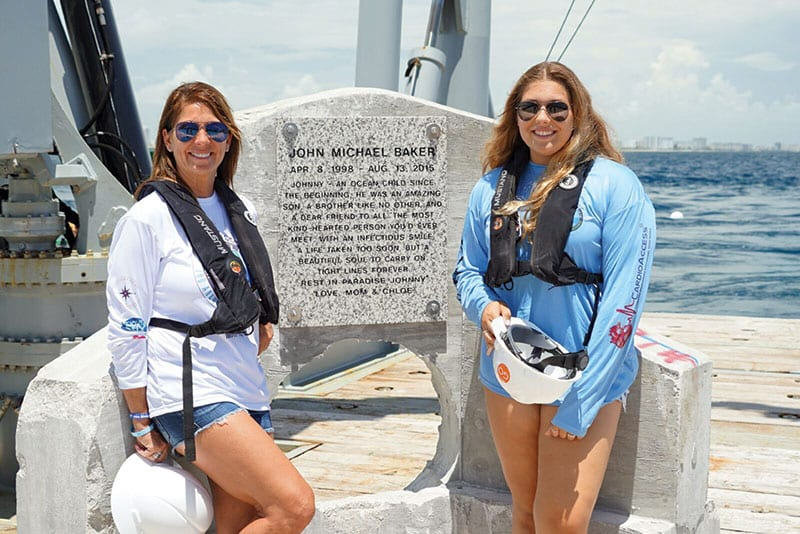 Johnny's mother and sister, Jamie and Chloe Baker, in front of memorial plaque ready to be deployed