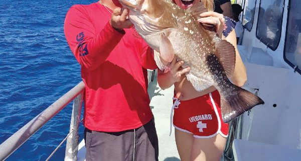 Capt Rod helps guest show off her big red grouper caught aboard the Catch My Drift.