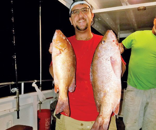 Chris with a pair of nice mangrove snappers caught with Fishing Headquarters.