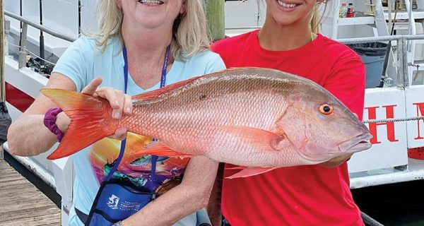 Betty Bauman and Kaylee with a nice mutton caught aboard the Catch My Drift.
