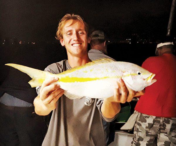 Matt with a nice yellowtail he caught night fishing on Catch My Drift.