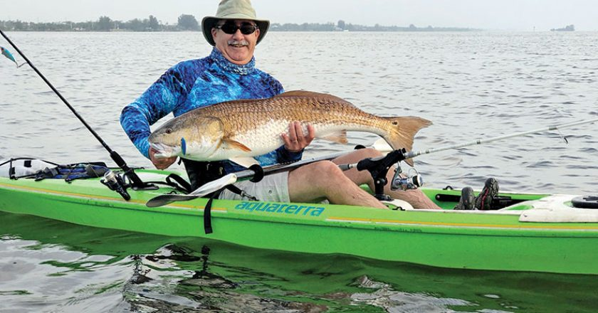 Dwight Bost with a huge redfish caught on the Indian River on a blue back Skitter Walk topwater plug. The red came partially out of the water to take the plug — an exciting start to an exhilarating fight!
