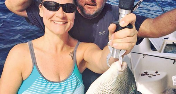 Amy Hayes getting some trigger fish action with Capt. Jason.