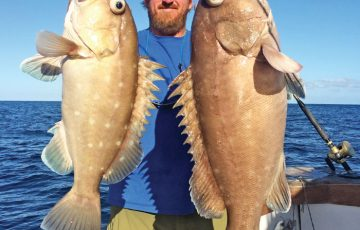 Capt. Adam with a pair of big snowy groupers caught with New Lattitude Sportfishing.