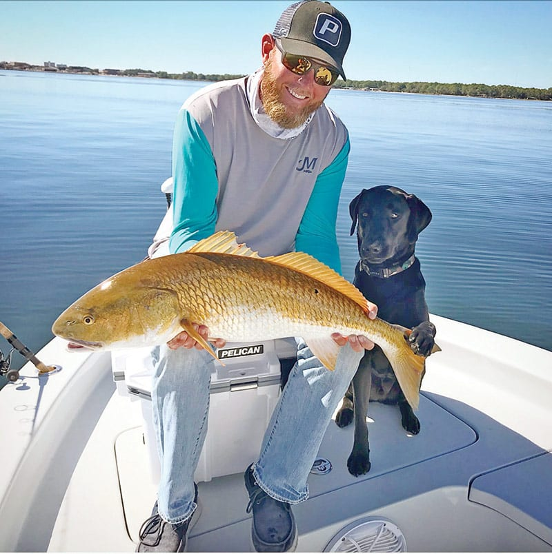 Capt. Jordan Todd and Murphy dog with a bull red sight fished.