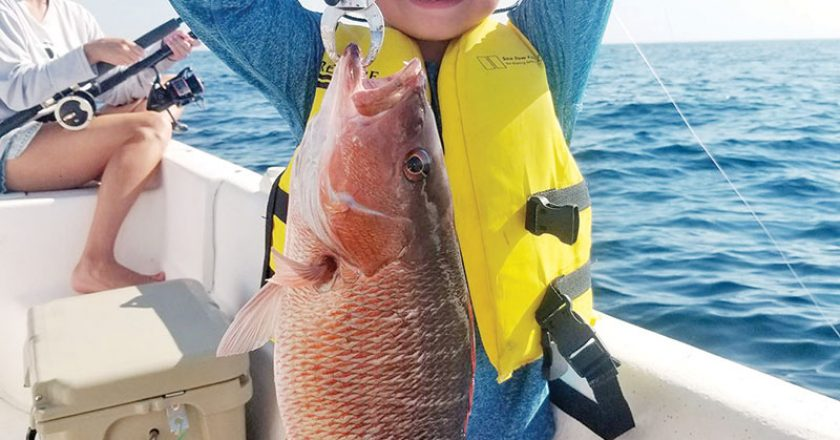 Gavin Gonterman from Corpus Christi, Texas cranking up mangrove snapper with Capt. Jason.