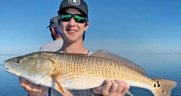 Jackson Williams, from Atlanta, with his first ever redfish, caught in St. Joe Bay.