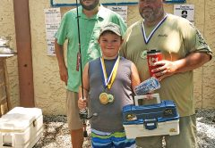Pinfish Grand National Winner Caleb Hicks being awarded his medal, tackle box, hat and new fishing rod.