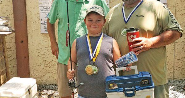Pinfish Grand National Winner Caleb Hicks being awarded his medal, tackle box, hat and new fishing rod.