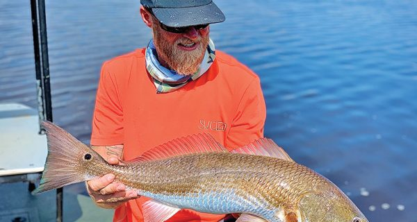 Scott Burgess from Tallahassee with a beautiful upper slot redfish caught on a Slayer INC stick bait in pearl white color.