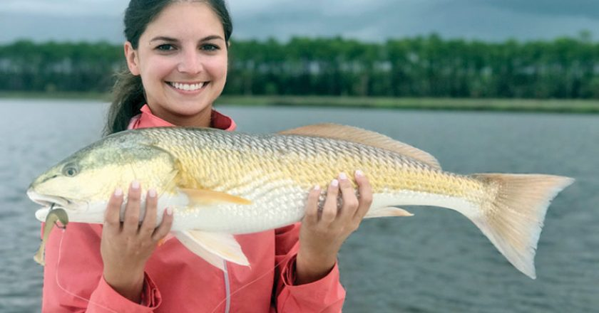 Abbey Posey with a stud 27 inch redfish caught on the new Storm Coastal paddle tail in mullet color.