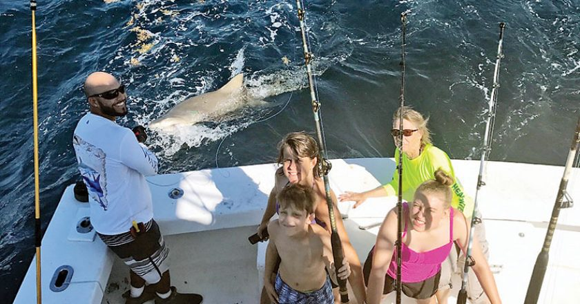 Mindy and kids with a monster lemon shark caught with New Lattitude Sportfishing.
