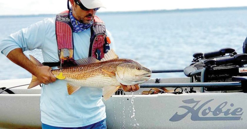 Benton Parrott, paddle power editorial writer, shows off a nice redfish caught from his Hobie kayak.