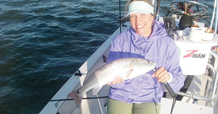 Kim catches a fine example of a Mosquito Lagoon redfish on a recent trip with Capt. Mark Wright.