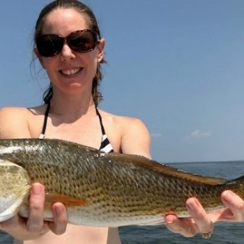 Julia Mahatekar proudly displays her redfish taken on the Eastern Shore of Mobile Bay.