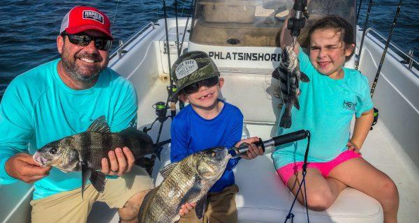 Ryan, Ryker and Ocean holding up black drum.